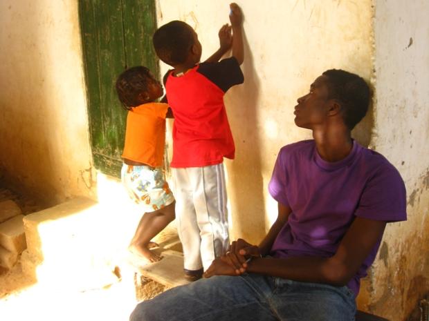 Barn som ritar på vägg i Serekunda, Gambia.